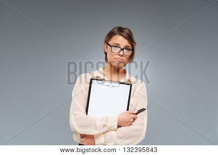 Close-up portrait of a sad melancholy girl holding folder over gray background