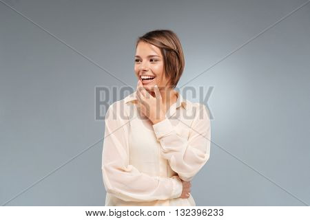 Laughing beautiful girl looking away isolated on the gray background