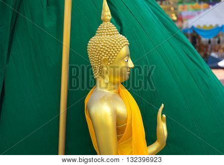 Gold buddha statue on green background at Thailand