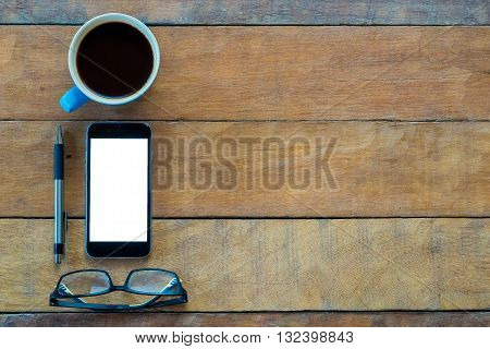 Desk table with blank screen smarphone cup of coffee and pen .Flat lay photo.Top view with copy space