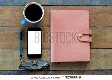 Flat lay shot of office workspace with blank screen smartphone leather notebook cup of coffee and pen.Top view with copy space