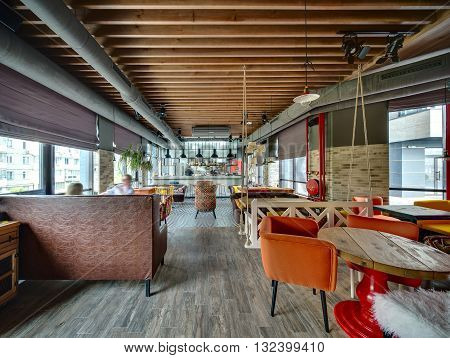 Hall in a loft style in a mexican restaurant with open kitchen on the background. On the left there is a brown sofa, wooden tables with multi-colored chairs, a dark sofa with color pillows, a plant. On the right there is a rounded wooden table