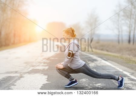 Running stretching. Woman stretching leg as warm-up before run with sport activity.