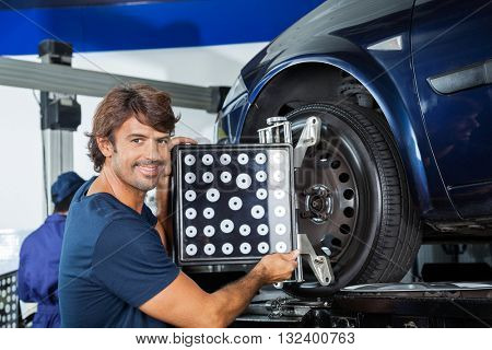 Smiling Mechanic Adjusting Alignment Machine On Car
