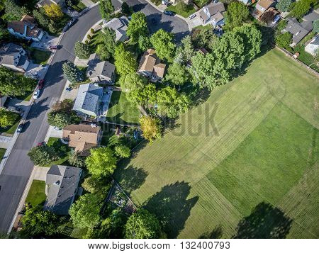 FORT COLLINS, CO, USA - MAY 23, 2016: Aerial  view of residential neighborhood in springtime with a large mowed grass field.