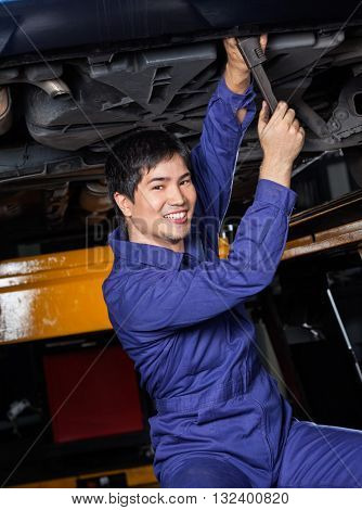 Confident Mechanic Repairing Underneath Car