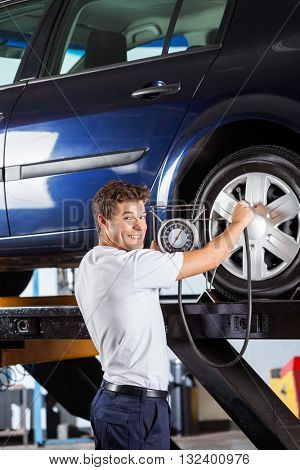 Smiling Mechanic Holding Gauge While Refilling Car Tire