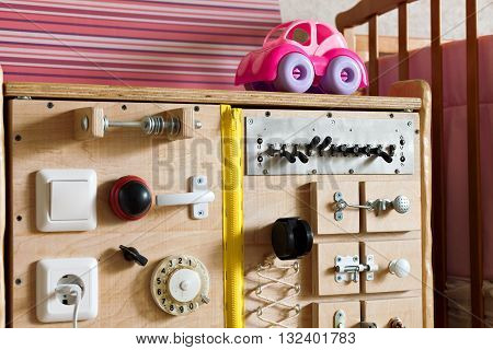 Playground structure of wood in the room. Toy with switches, buttons and levers. handmade Bizibord. Developing board motor skills of the child. Methods of Montessori. A room with toys for girls.