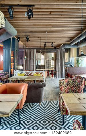 Amazing mexican restaurant in a loft style. In front of the room there are several wooden tables with multi-colored sofas and chairs. On the sofas there are color pillows. On the back side of the room there is a cupboard with glass doors