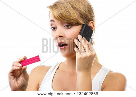 Unhappy worried sad woman holding pregnancy test and talking on mobile phone informing someone about positive result test unwanted pregnancy