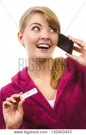 Happy delighted woman wearing purple bathrobe showing pregnancy test and talking on mobile phone informing someone about positive result test expecting for baby