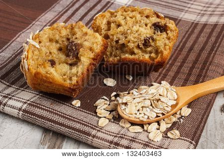 Fresh muffin with oatmeal baked with wholemeal flour on checkered tablecloth concept of delicious healthy dessert or snack