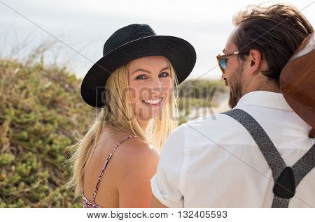 Portrait of happy young woman looking at camera. Cheerful woman wearing black straw hat while going at beach. Close up face of smiling girl with her boyfriend outdoor.