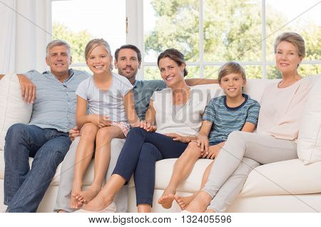 Portrait of happy family sitting on couch at home. Smiling parents, grandparents and happy children looking at camera. Portrait of extended family group sitting together.