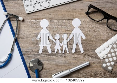 Top view of family paper chain on a doctor desk. Medical worktable with keyboard, blue stethoscope, pills and eyeglasses. Family healthcare, medicine and insurance concept.