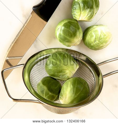 Brussel sprouts in a sieve with a knife.