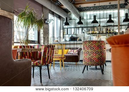 Charming hall in a loft style in a mexican restaurant with open kitchen on the background. In front of the kitchen there are wooden tables with multi-colored chairs and sofas. On the sofas there are color pillows. In the kitchen there is a rack