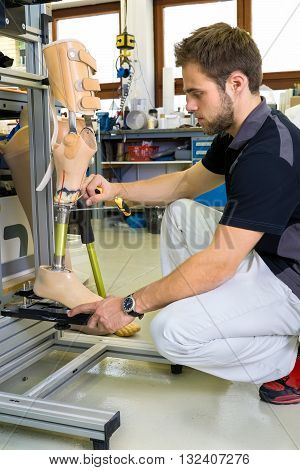 Young bearded man working on shin and knee section on prosthetic leg assembly in laboratory for research and development