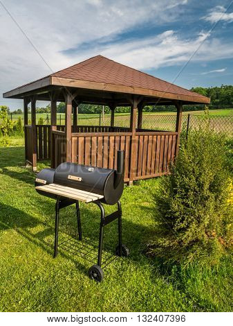 Wooden summer house with grill in the backyard