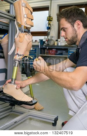 Single adult technician using tool to adjust length and stability on prosthetic leg assembly in workshop