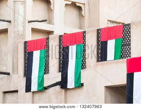 The flag of The United Arab Emirates draped over a traditional Arabic house in Dubai.