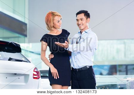 Asian couple choosing luxury SUV car in auto dealership