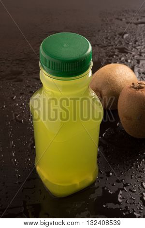 Kiwi fruit juice with fresh kiwi on a wet dark background
