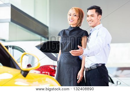 Asian couple choosing luxury sports car in auto dealership
