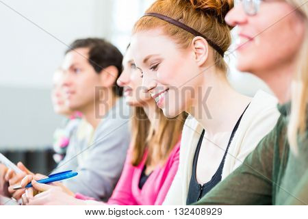 College students making lesson notes in university auditorium
