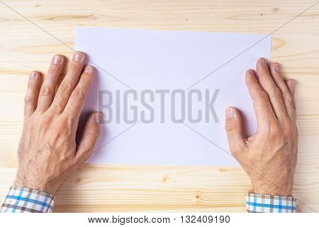 Graphic designer with blank paper on office desk as copy space blank space for design artwork or text placement top view.