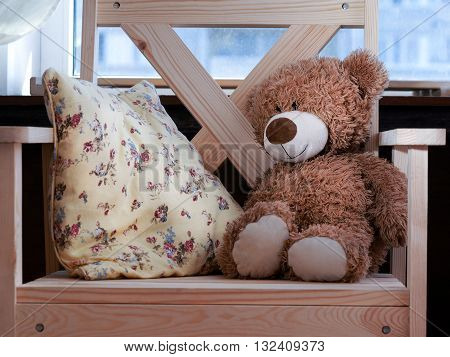 On a wooden chair cushion and toy - a teddy bear. Chair near the window. Concept - comfort, home furnishings, quiet, waiting for baby