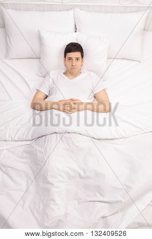 Vertical shot of a worried young man laying in bed and contemplating something