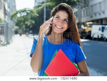 Laughing caucasian female student at phone outdoor in city with buildings and street in the background