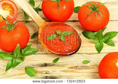 tomatoes and wooden ladle with tomato sauce on wood