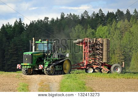 SALO, FINLAND - MAY 27, 2016: John Deere 9520T agricultural crawler tractor and cultivator moving along dirt road in rural spring landscape on the way to cultivate a field.