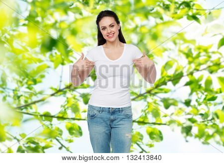 advertisement, clothing and people concept - happy smiling young woman or teenage girl in white t-shirt pointing finger to herself over green natural background