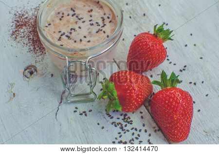 Homemade yogurt in a jar with strawberry seeds and cacao. Dessert with strawberries on a white wooden background. Fresh strawberry with yogurt. Selective focus. Shallow depth of field. Horizontal.