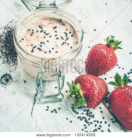 Homemade yogurt in a jar with strawberry seeds and cacao. Dessert with strawberries on a white wooden background. Fresh juicy strawberry with yogurt. Selective focus. Shallow depth of field. Square.