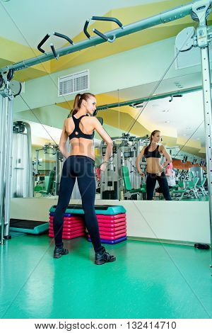 Athletic young woman is training arm and shoulder muscles at the gym. Active lifestyle, bodycare. Fitness equipment.
