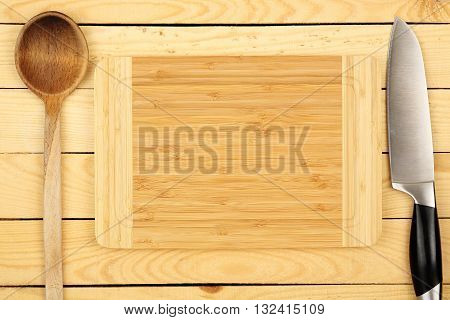 cutting board with knife and ladle on wood