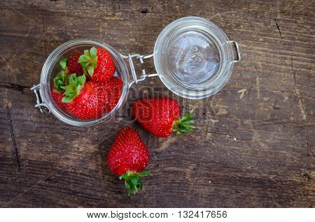 Red berry strawberry in glass jar on old rustic wooden background. Background from freshly harvested strawberries. Strawberry background. Selective focus. Shallow depth of field. Horizontal.