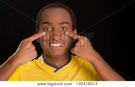 Headshot dark skinned male wearing yellow football shirt in front of black background, using fingers applying facepaint to cheeks.