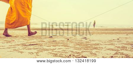 journey concept vintage tone image of blur buddhism monk and sea in background.(selective focus on sand)