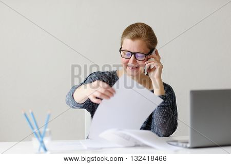 Smiling business woman sitting at office Desk and working with laptop and documents