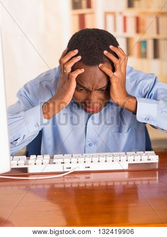 Young handsome man wearing blue office shirt sitting by computer leaning forwards over keyboard holding head in disbelief and frustration.