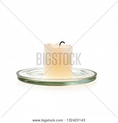 White wax candle on a glass stand. The calcine thick with charred candle wick stands on a glass stand. Isolated on white background