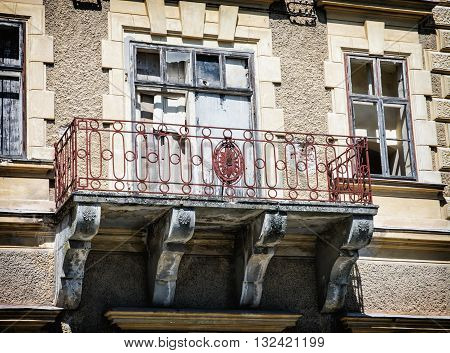 Close up photo of beautiful old house with artistic balcony. Architectural theme. Abandoned house. Broken windows. Architectural elements.
