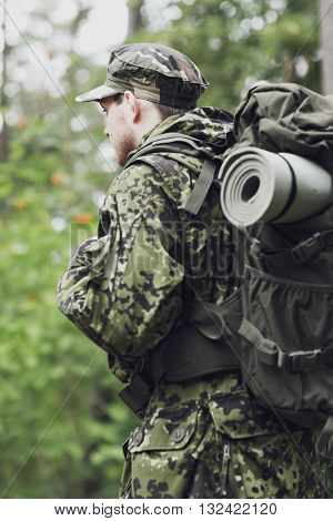 war, hiking, army and people concept - young soldier, ranger or hunter with backpack walking in forest