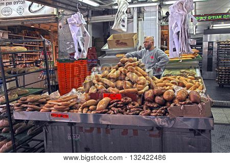 TEL AVIV, ISRAEL - APRIL 3, 2016: An unidentified man sells bread on market stall at Carmel Market in Tel Aviv, Israel.