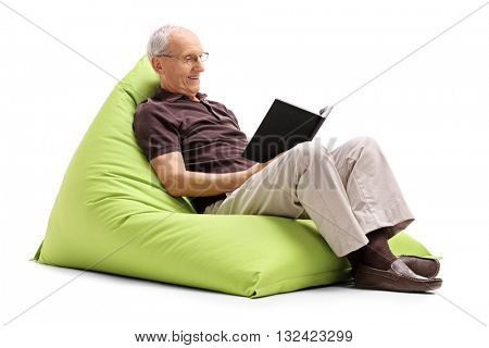 Senior gentleman reading a book and relaxing seated on a green beanbag isolated on white background
